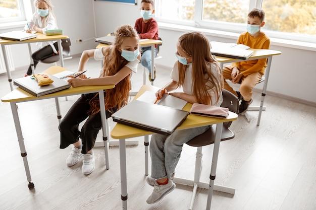 Bambini della scuola impegnati con i quaderni che scrivono insieme il test