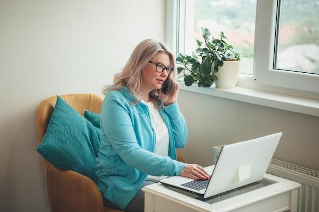 Donna maggiore occupata con occhiali e capelli biondi, parlando al telefono e lavorando da casa al computer portatile