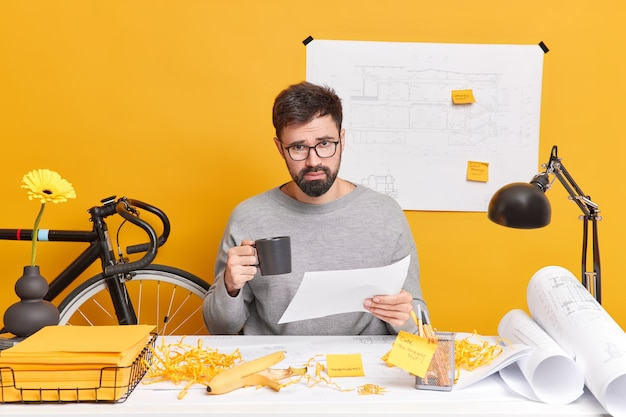L'impiegato maschio barbuto serio occupato fa rapporto tiene documento cartaceo beve caffè ha schizzi e progetti sparsi sulla scrivania