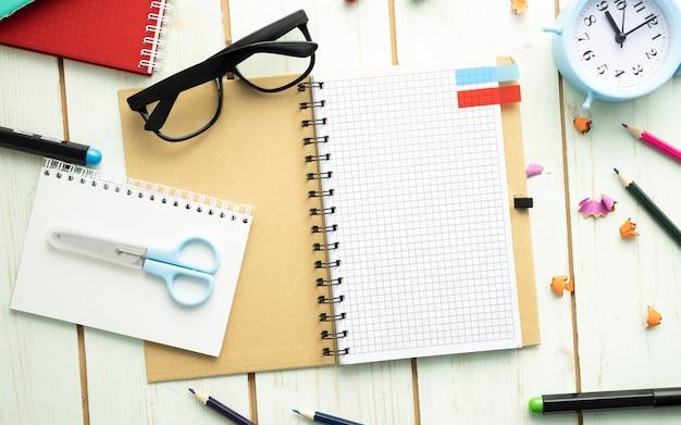 Scrittorio dello studente occupato con il taccuino aperto in bianco