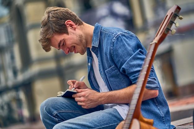 Un musicista di talento e impegnato scrive una nuova canzone sul taccuino