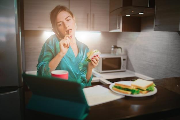 Donna impegnata a mangiare, bere caffè, parlare al telefono, lavorare al laptop allo stesso tempo. imprenditrice facendo più attività