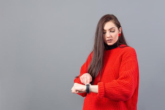 Donna impegnata in maglione rosso preoccupata guardando il suo orologio da polso, femmina in ritardo, isolato su grigio