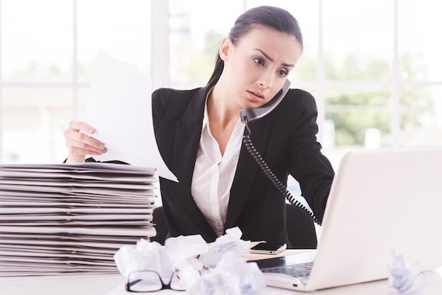 Occupato a lavorare. fiduciosa giovane donna in abiti da cerimonia con documenti e parlando al telefono mentre è seduta al suo posto di lavoro