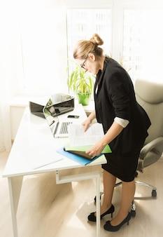 Giovane donna d'affari impegnata che lavora con le carte in ufficio