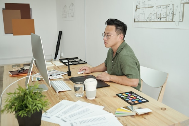 Giovane designer impegnato seduto davanti al monitor del computer