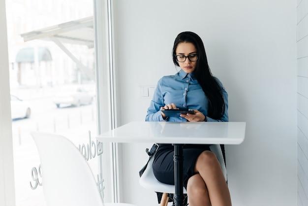 Una ragazza impegnata con una camicia blu e occhiali è seduta in un bar e guarda il tablet