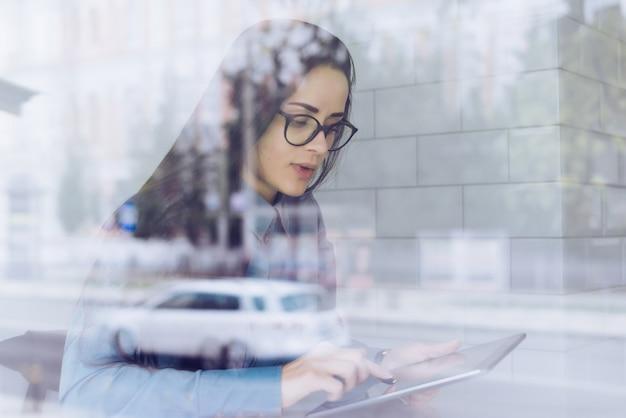 Libero professionista giovane ragazza impegnata in una camicia blu e occhiali guarda il tablet