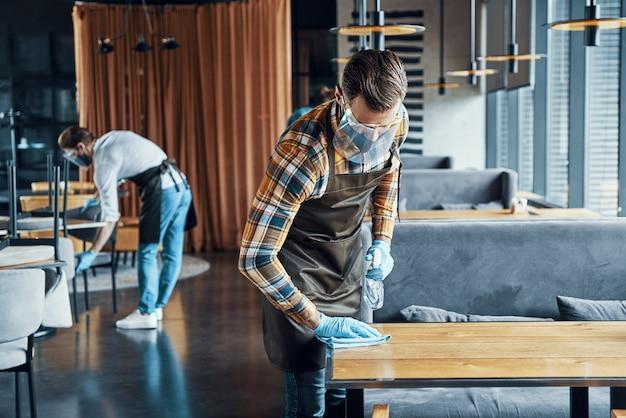 Giovani camerieri maschi indaffarati in abiti da lavoro protettivi che spruzzano disinfettante sui tavoli del ristorante