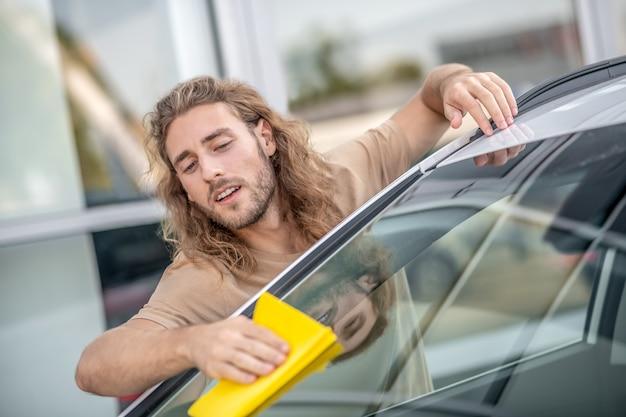 Occupato. giovane che pulisce il parabrezza dell'auto e sembra coinvolto