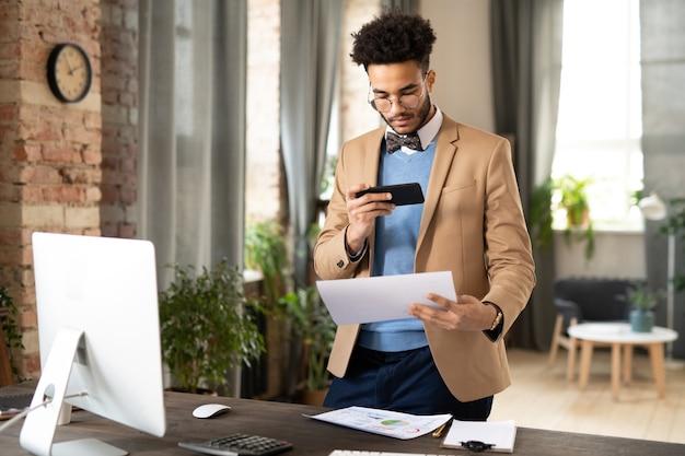 Giovane impiegato di razza mista impegnato in giacca elegante in piedi alla scrivania e fotografare documenti sullo smartphone in ufficio