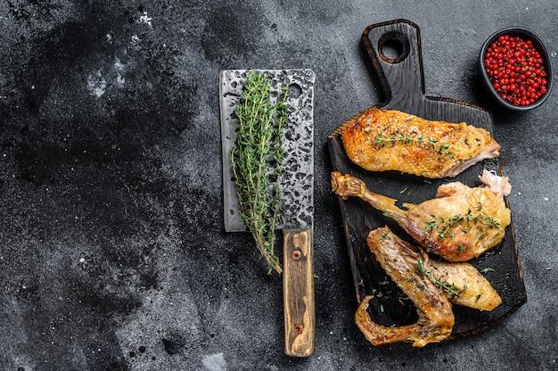 Anatra al forno macellata, filetto di petto, ala, coscia. sfondo nero. vista dall'alto. copia spazio.