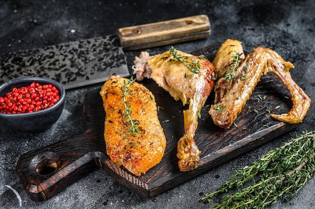 Anatra al forno macellata, filetto di petto, ala, coscia. sfondo nero. vista dall'alto.