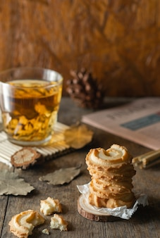 Biscotti al burro impilati e un bicchiere di tè su sfondo tavolo in legno, foto verticale.