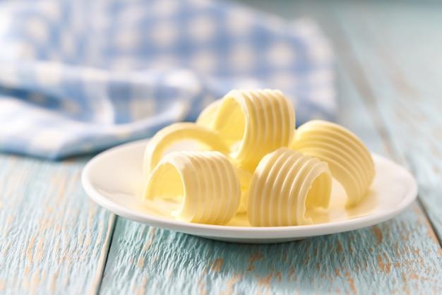 Il burro arriccia o arriva a fiumi la ciotola ceramica su una tavola di legno blu, fuoco selettivo.