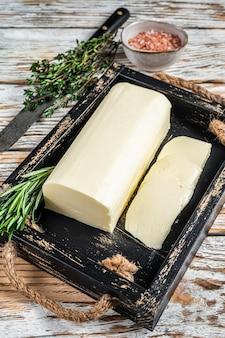 Burro margarina blocco in un vassoio di legno con erbe aromatiche. fondo di legno bianco. vista dall'alto.