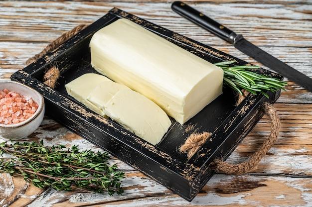 Burro margarina in blocco in un vassoio di legno con erbe aromatiche