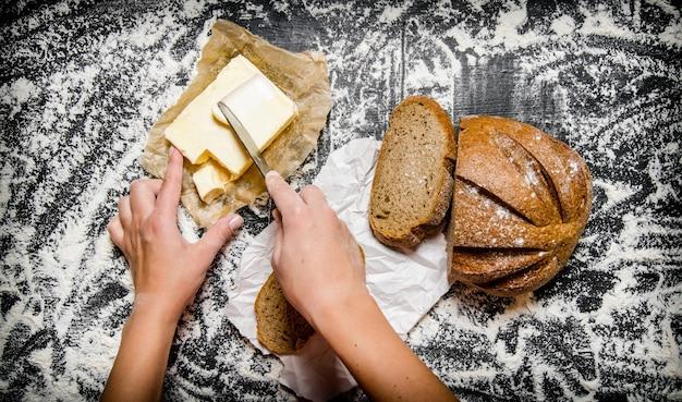 Imburrare il pane con il burro su una tavola con la farina. vista dall'alto