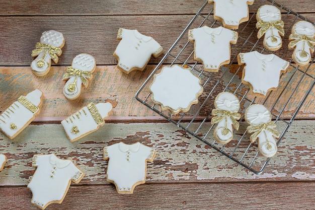 Biscotti al burro ricoperti di ghiaccia reale. sotto forma di body per bebè, biberon e sonaglio (vista dall'alto).