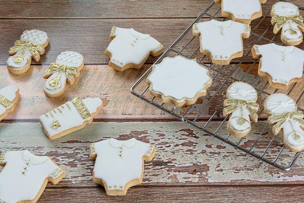 Biscotti al burro ricoperti di ghiaccia reale. sotto forma di body per bebè, biberon e sonaglio.