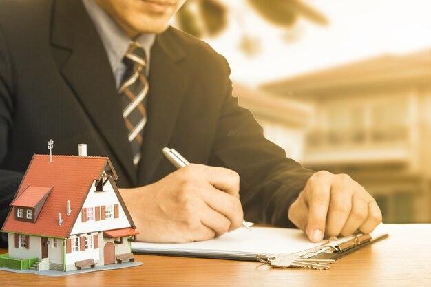 Acquista casa. l'uomo d'affari calcola e pianifica la tua buona proprietà con la proprietà dell'agenzia immobiliare