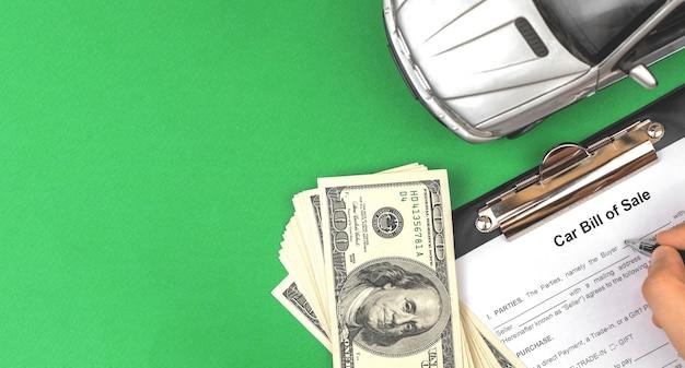 Acquista una nuova auto, compilando e firmando i documenti e i documenti. contratto di compravendita. desktop da ufficio verde, soldi e macchinina, foto vista dall'alto