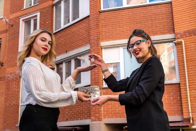 L'acquirente dà al venditore dollari sullo sfondo della casa. comprare o affittare una nuova casa