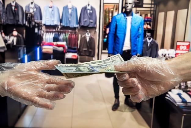 L'acquirente con guanti di plastica dà all'acquirente dollari per la merce nel negozio di abbigliamento. concetto di igiene. pandemia dovuta a un nuovo pericoloso virus. coronavirus