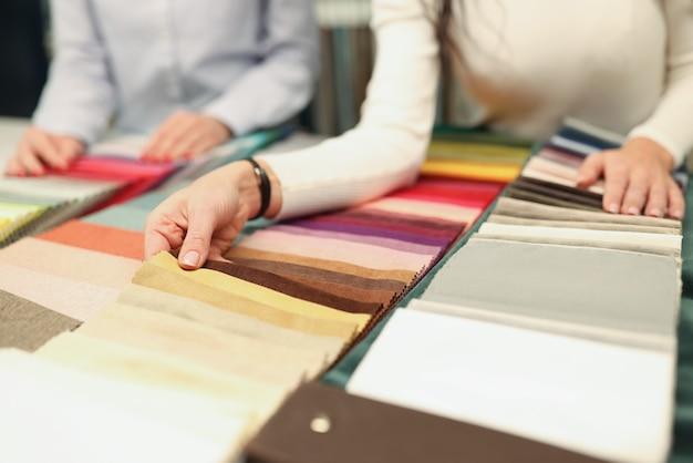 Acquirente e venditore scelgono il colore del concetto di sartoria personalizzata del tessuto