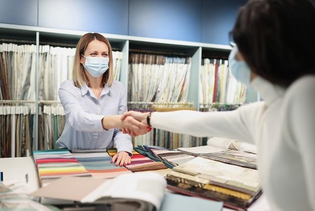 Acquirente e venditore in maschere mediche protettive si stringono la mano nel servizio clienti sicuro del salone dei tessuti