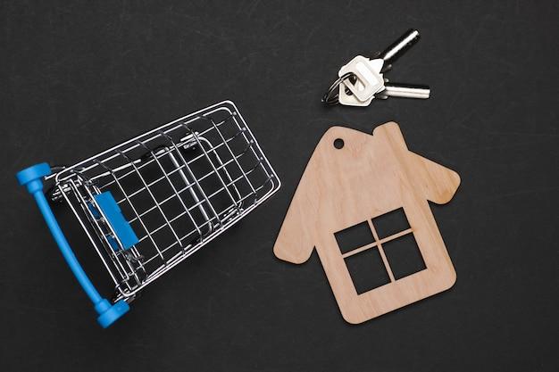 Acquisto di una casa, natura morta in miniatura. carrello della spesa con figura di casa su sfondo nero.