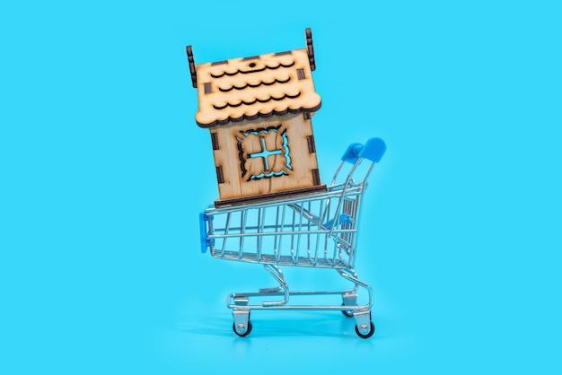 Acquisto di una casa e proprietà, vendita di una casa, concetto di affari immobiliari, nuova casa in un cesto su un tavolo blu.