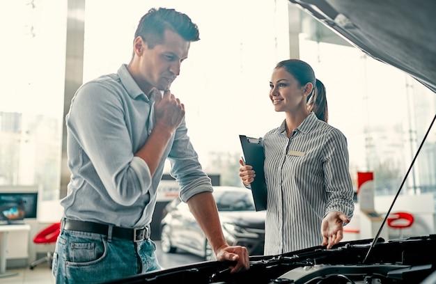 Comprare la mia prima macchina. giovane commessa di auto in piedi presso la concessionaria che racconta le caratteristiche dell'auto sotto il cofano al bell'uomo.