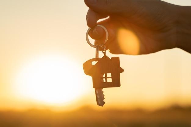 Acquistando o affittando il concetto di casa residenziale la mano di una donna tiene una chiave con un portachiavi a forma di...