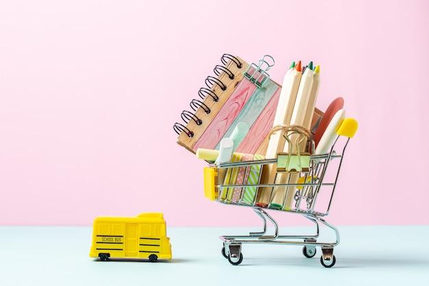 Acquisto di materiale scolastico, matite, quaderno e cancelleria per pastelli per bambini in un carrello della spesa con