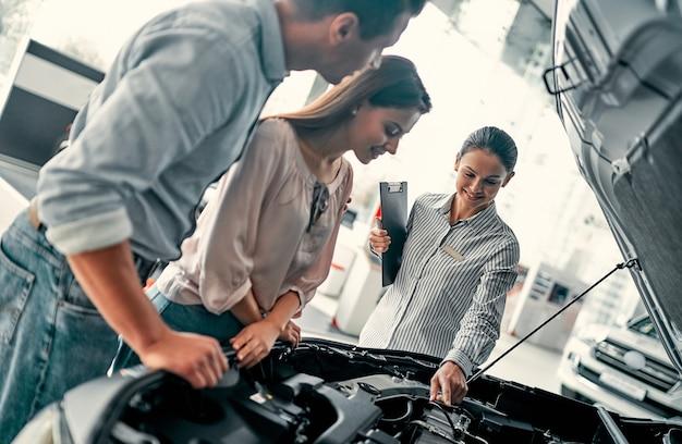 Comprare la loro prima auto insieme. giovane commessa di auto in piedi presso la concessionaria che racconta ai clienti le caratteristiche dell'auto sotto il cofano.