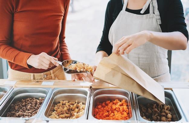 Acquisto in un negozio a rifiuti zero o in un negozio di alimentari senza plastica assistente di negozio che aiuta il cliente del servizio