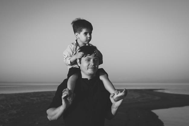 Bw ritratto di un simpatico ragazzo di 3 anni sul collo di suo padre che cammina sulla spiaggia con l'illuminazione del tramonto