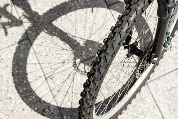 Sagoma dell'ombra della ruota anteriore in bicicletta e vista del pneumatico su sfondo urbano in cemento