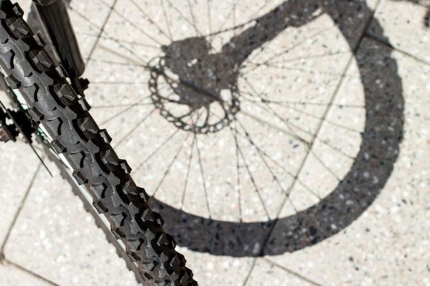 Sagoma dell'ombra della ruota anteriore in bicicletta e vista del pneumatico sulla superficie delle piastrelle di cemento urbano