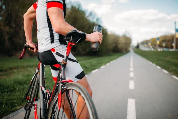 Ciclista in casco e abbigliamento sportivo in allenamento in bicicletta