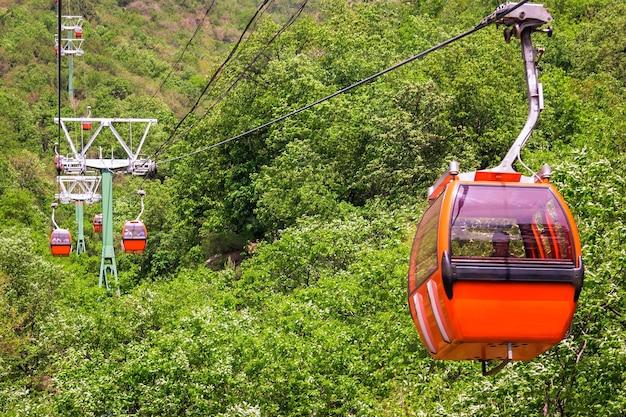 Cabina di colore arancione della funivia sullo sfondo del paesaggio montano del sito della grande muraglia cinese mutianyu