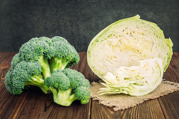 Cavolo, broccoli e cavolfiore su fondo in legno.