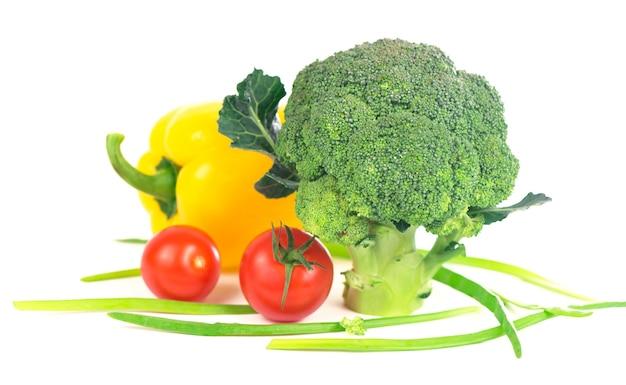 Cavolo broccolo con pomodori e foglie verdi isolate su superficie bianca