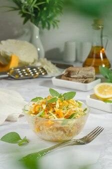 Insalata di cavolo cappuccio, carote grattugiate e zucca con burro, basilico e erbe aromatiche al rosmarino, con bokeh di verdure