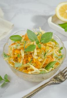Insalata di cavolo cappuccio, carote grattugiate e zucca con primo piano olio, basilico e rosmarino