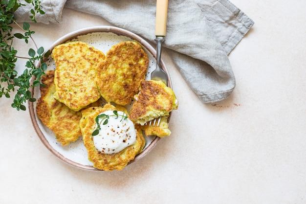 Frittelle di cavolo o zucchine su piatto in ceramica cibo vegetariano sano