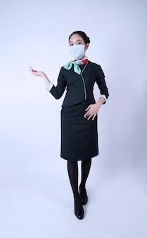 Equipaggio di cabina o hostess di volo con maschera facciale in caso di pandemia covid 19. l'assistente di volo indossa una maschera medica per prevenire l'infezione da coronavirus. nuovo stile di vita normale nel settore delle compagnie aeree. donna graziosa hostess.