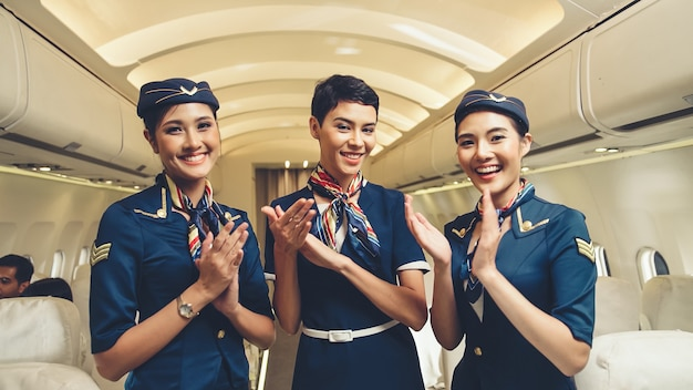 Equipaggio di cabina che applaude le mani in aereo. trasporto aereo e concetto di turismo.