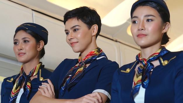 Equipaggio di cabina che balla con gioia in aereo. trasporto aereo e concetto di turismo.